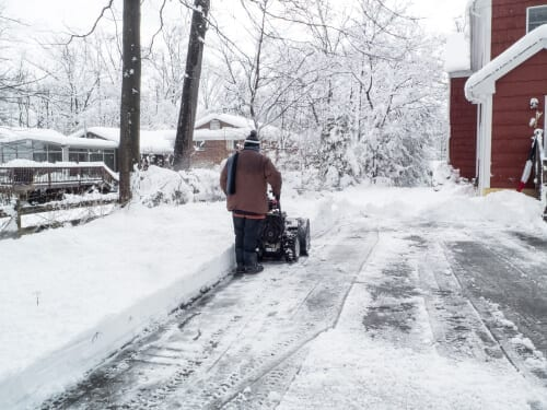 man cleaning the driveway with snowblower after the snowstorm