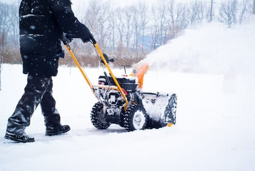 man cleans snow from sidewalks with snowblower